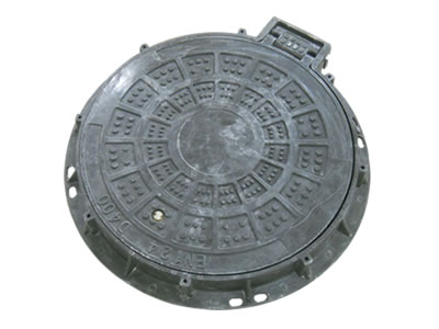 A black round FRP manhole cover with rings, round shapes, frame and projected joint; frame has some stems.