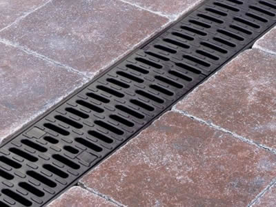 Two row drainage hole cast iron grating with many oval blocks.