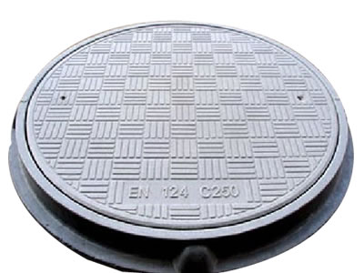 A gray round FRP manhole cover with many strips, two drainage holes and frame; four strips form a square.
