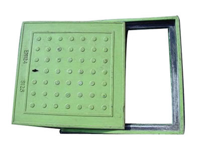 A green square FRP manhole cover with many round blocks, a drainage hole and a frame.