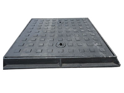 A rectangle cast iron manhole cover with square blocks, two drainage holes and frame.