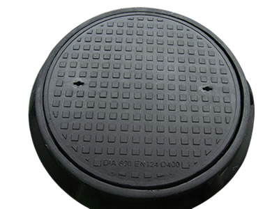 A black round FRP manhole cover with many square blocks, two drainage holes and frame which diameter is 600 mm.
