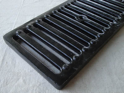A rectangle cast iron grating with one row drainage holes and two row round projections.